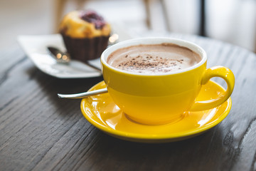 hot chocolate in yellow mug on the wooden table.