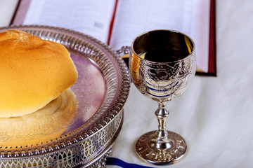Close up of bread and a cup of red wine on wooden table for communion, Christian concept for reminder of Jesus