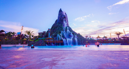 Universal´s Volcano Bay waterpark during the sunset on 14th august 2017. The main volcano waterfall with sliders at sunset scene and people taking a bath in the waves pool.