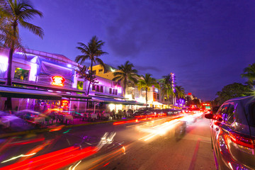 Ocean Drive scene at sunset with lights, palm trees, cars and people having fun, Miami beach. Art Deco style hotels and restaurants at sunset on Ocean Drive, world famous destination for its nightlife