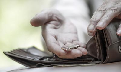 eine Person zählt die wenigen Münzen in ihrer Geldbörse