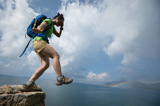 Woman walking off of a cliff edge with the eyes covered. .