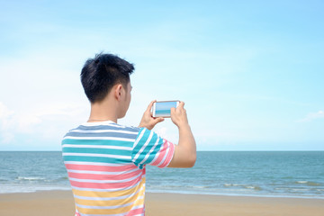 Young man taking photo at the beach Sea in summer.Traveler vacation concept.