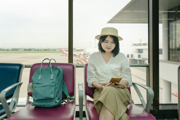 Asian woman passenger using smartphone at airport terminal sitting with  backpack waiting for her flight to travel on weekend. Traveler concept.