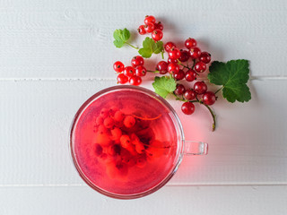 Freshly prepared refreshing drink of red currant berries and a sprig of berries on a white wooden table. The view from the top. Flat lay.