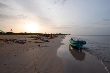Small fishing boat on shore at sunset on Nilaveli beach in Trincomalee Sri Lanka Asia