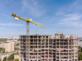 high yellow crane near residential building under construction against blue sky background