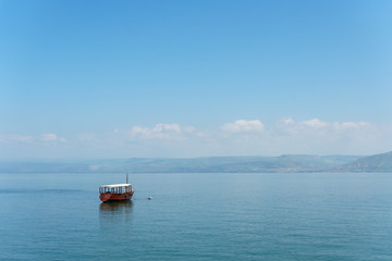 Old boat on Sea of Galilee in Israel at foggy spring day.