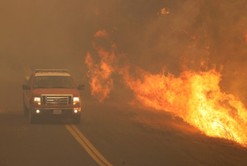 A firetruck rushes past flames that overran a road at the River Fire in Lakeport