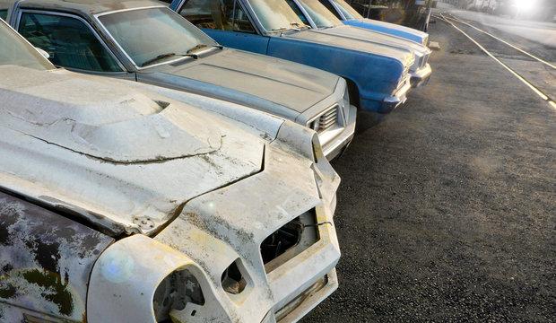 old rusty cars in auto salvage junkyard