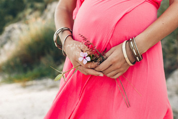close up of tummy of pregnant woman wearing long red dress outdoors