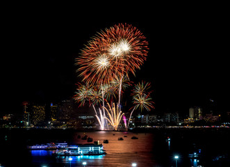 Fireworks explored over cityscape at night in sea port in Pattaya.Holiday festive celebration background.