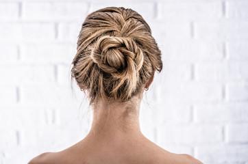 Head of a young woman from behind. Rear view braid hairdo. Hair bun