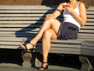 Woman in a short skirt and black sandals with high heels sitting with a red smartphone in her hand on the wooden bench. Girl with beautiful long legs, online dating, slim sexy body
