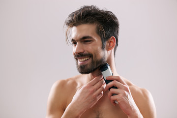 Young man is shaving his beard with electric razor.