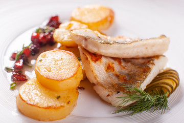 Roasted cod, codfish with baked potatoes and vegetables with pickled cucumber and herbs sauce on a white background Restaurant serving. restaurant menu