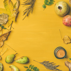 Fall background, texture, pattern. Flat-lay of Autumn harvest fruit, espresso cup and leaves over mustard yellow table, top view, copy space, square crop. Pomegranates, pears. Thanksgiving day concept