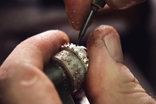 Close up of the hands of a goldsmith while he is making a diamond ring. Concept: jewelry, gold, fashion