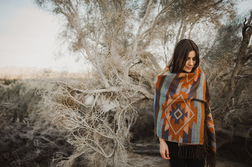 Beautiful hipster traveler girl in gypsy look in desert nature, lookig side.  Artistic photo of young hipster traveler girl in gypsy look, in Coachella Valley in a desert valley in Southern California