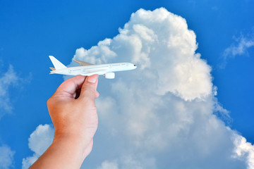 toy airplane in hand on beautiful sky with cloud background in concept travel around the world