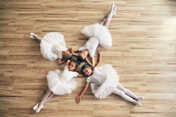 Top view of four dancers lying on the parquet floor of a dance school, who rest after exercising. Concept of: team, teaching, ambition, relaxation.