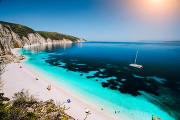 Fteri beach, Cephalonia Kefalonia, Greece. White catamaran yacht in clear blue sea water. Tourists on sandy beach near azure lagoon