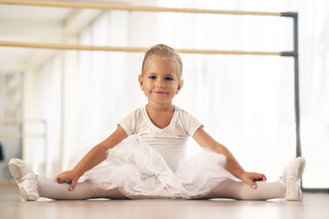 Portrait of a beautiful very young girl, in a dance school wearing a white tutu, she trains alone to learn new dance steps. Concept of: ambition, education, elegance and love for the dance...