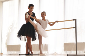 A teacher of classical dance teaches some steps to his young student who wants to learn how to dance and in the background the other little girls who listen. Concept of: ambition, education, teaching