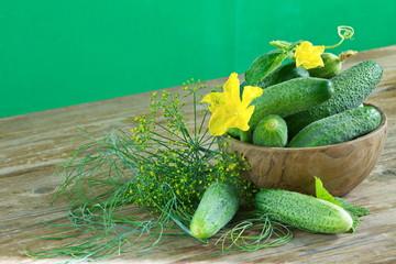 Свежий урожай огурцов с желтыми цветами в деревянной миске на столе