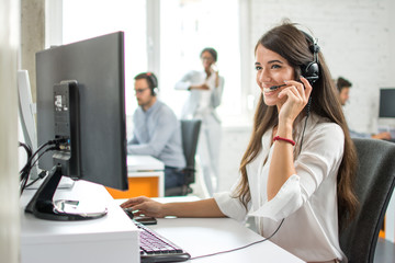 Friendly female customer service helpline operator working on computer in ofice