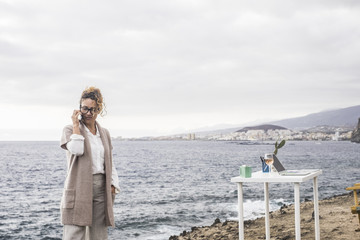 beautiful lady at work with mobile phone and laptop on the desktop in alternative office outdoor in front of the ocean. calling for business. elegant dress and serious hair. wine on the table