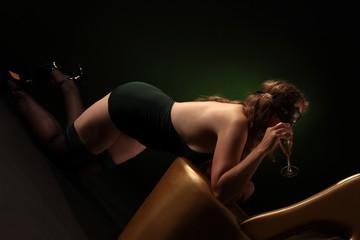 Frau in grünen Dessous trinkt Sekt