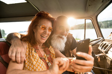 Old hipster couple using a smartphone inside their camper van
