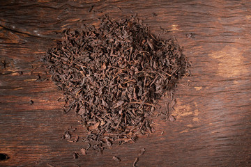 Falling dried black tea leaves isolated on wooden table