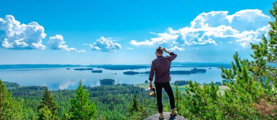 Ein Mann schaut auf der Spitze des Berges auf den See Dellen
