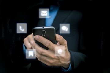 business men holding mobile smartphone in hand - surrounded by web and chat internet signs and symbols