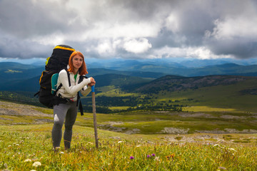 Atmospheric moment in mountains. Hiking woman with backpack traveler on top of mountains. Stylish woman hiking, in the background a green forest, field and high mountains..