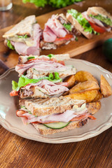 Sandwiches with ham, cheese, tomatoes, lettuce and cucumber