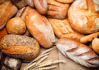 Foto auf Acrylglas Brot heap of fresh baked bread on wooden background