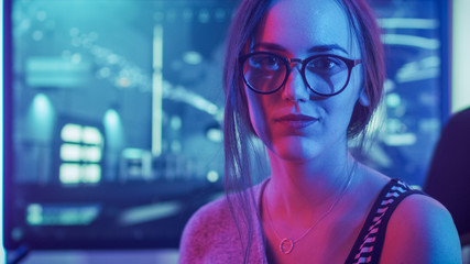 Portrait of the Beautiful Young Pro Gamer Girl Sitting at Her Personal Computer and Looks into Camera Smiling. Attractive Geek Girl Player Wearing Glasses in the Room Lit by Neon Lights.