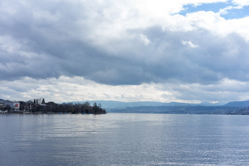 stormy clouds and calm water over lake zurich in switzerland