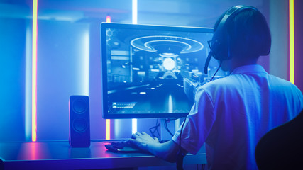 Arc Shot of the Professional Gamer Playing in First-Person Shooter Online Video Game on His Personal Computer. He's Talking with His Team Through Headset. Room Lit by Neon Lights in Retro Arcade Style