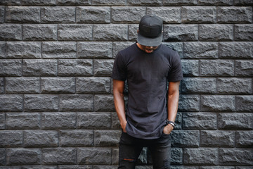 Handsome african american man in blank black t-shirt standing against brick wall Wall mural