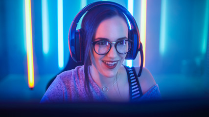 Beautiful Friendly Pro Gamer Girl Does Video Game Gameplay stream, Wearing Headset Talks / Chats with Her Fans and Team into Headphones Microphone and Smiling. Background Cool Neon Retro Colors.