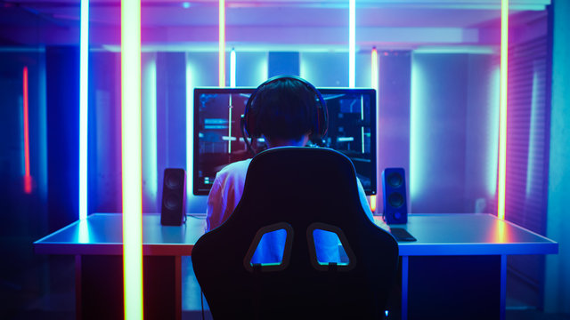 Back View Shot of the Beautiful Professional Gamer Girl Putting on Headset and Starts Playing Online Video Game on Her Personal Computer. Cute Casual Geek Girl. Lit by Neon Lamps in Retro Arcade Style