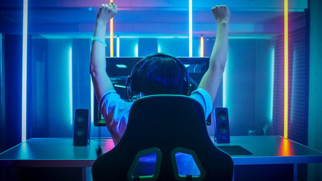 Professional Gamer Playing and Winning in First-Person Shooter Online Video Game on His Personal Computer. Footage Fade out into Bokeh. Room Lit by Neon Lights in Retro Arcade Style. Cyber Sport.