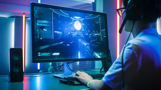 Back View Shot of Professional Gamer Playing in First-Person Shooter Online Video Game on His Personal Computer. He's Talking with His Team Through Headset. Lit by Neon Lights in Retro Arcade Style.