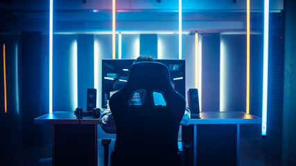 Professional Gamer Playing in First-Person Shooter Online Video Game on His Personal Computer. Room Lit by Neon Lights in Retro Arcade Style. Cyber Sport Championship.