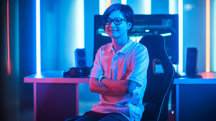Shot of the Professional Gamer Sitting on His Gaming Chair and Smiling into Camera. Personal Computer. Room Lit by Neon Lights in Retro Arcade Style. Online Cyber e-Sport. Crossed Arms.