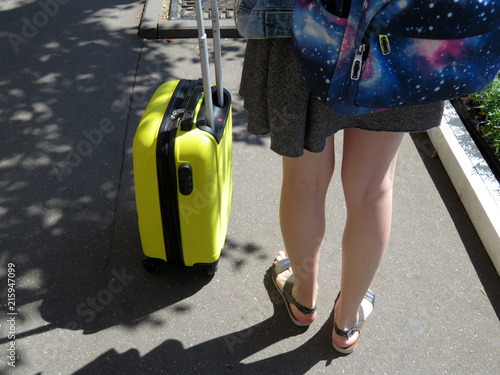 5faf3e3ea36d Female legs in sandals near the yellow travel suitcase on wheels. Girl